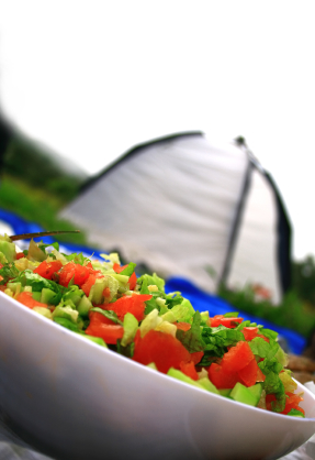 Healthfully Eating on Your Camping Trip As summer nears, the camping season is again upon us. There are few things more revitalizing than a weekend (or week) in the woods with family or friends. And while camping comes with varying degrees of exercise, whether through backpacking into the wilderness or spending a few hours paddling a canoe, it's important not to sabotage a piece of your health for the peace of the outdoors. To stay on top of your goals, spend some extra time planning a healthy menu of great camp foods. Here are some ideas: Fruits and Vegetables – Many fruits and vegetables can last up to three days unrefrigerated, if left uncut until you are ready to eat them. Some good choices are peppers, onions, carrots, bananas and apples. Sweet potatoes and various squashes will also stay fresh and yet are easy to prepare, either on a grill or in some boiling water. Nuts and Dried Fruits – If you're active while camping, it's important to maintain your energy while on-the-go. Keeping small bags of nuts and dried foods nearby will stave off hunger and provide a healthful, lasting snack. There a few high-quality energy bars out there as well. Frozen Foods – If you have the luxury of bringing a cooler, you can pack boxes or bags of frozen veggies that double as ice packs, keeping other foods cool. Save these for the final day or days of your camping trip and you save a lot of room in your ice chest. A 'Heart'y Breakfast – Breakfast is still the most important meal of the day, even outdoors. But you don't have to cook up the kitchen sink to get full. Eggs with peppers and onions make great omelets, and turkey bacon is a sensible substitute for regular, more fatty bacon. Of course, whole grain breads and oatmeal have deserved places on your morning plate. The Open Fire – Nothing describes camping more than a campfire. There are several brands and styles of low-calorie hotdogs on the market (Hebrew National makes a 40-calorie hotdog), and you don't always need a bun with those. If you have some fisher-people camping with you, fresh fish is always a good choice for dinner. And you don't have to forgo the classic S'more – just budget it in your food journal like you would any other dessert (but you can opt for the low-fat version of graham crackers!).   Odds and Ends – Other great foods to have on hand include cans of beans, popcorn, cheese, honey, ears of fresh corn and fruit salad. You don't have to go for the over-processed, boxed stuff or pre-made frozen meals to eat healthy while camping. Just think fresh and refreshing – which is exactly like the outdoors, right? What other ideas and recipes do you have to share for healthful camping options? Share with us on the MyNetDiary Facebook page or in our Community Forum. We'd love to hear from you!