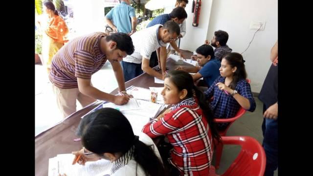 देहरादून के आई.एम.ए. ब्लड बैंक में आयोजित रक्तदान शिविर में रक्तदान का फॉर्म भरते लोग।
