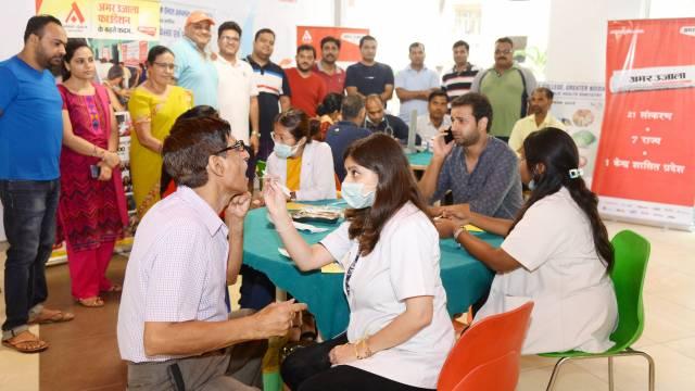 ग्रेटर नोएडा की सोसाइटी सुपरटेक इको विलेज- टू में आयोजित शिविर में दंत परीक्षण करते चिकित्सक