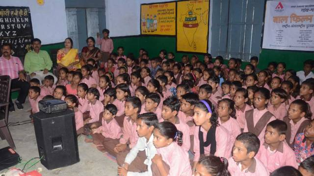 प्राथमिक/पूर्व माध्यमिक विद्यालय (समेकित) लेखराजपुर में 'करामाती कोट' नामक बाल फिल्म देखते बच्चे एवं शिक्षक