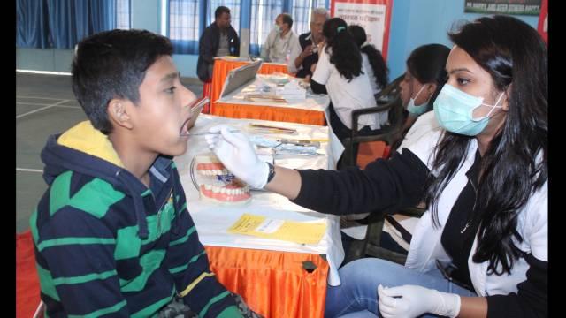 नोएडा के सेक्टर-46 स्थित सामुदायिक भवन मेंआयोजित शिविर में दंत परिक्षण करते चिकित्सक