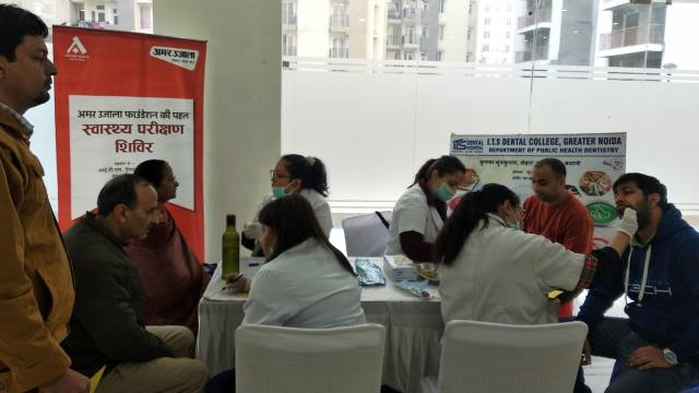 ग्रेटर नोएडावेस्ट की सोसायटी स्प्रिंग मिडोज में आयोजित शिविर में स्वास्थ्य परिक्षण करते चिकित्सक