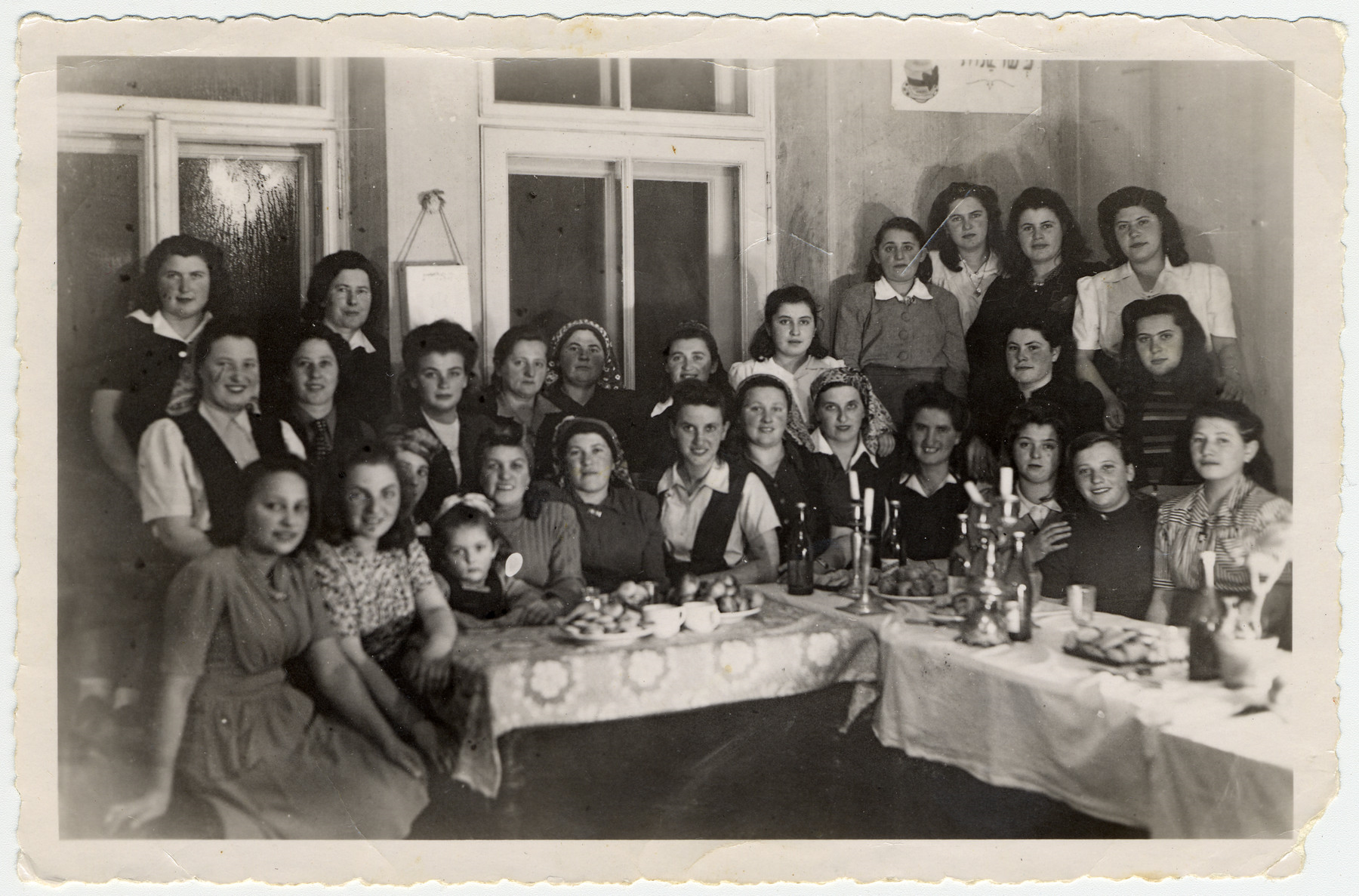 <p>Pho­to of Bnos Agu­dath Israel in the Bad Gad­stein Dis­placed Per­sons camp. Reli­gious Jew­ish women gath­er around a&nbsp;table set for the Sab­bath or a&nbsp;hol­i­day. Cour­tesy of Esther Klug and the Unit­ed States Holo­caust Memo­r­i­al&nbsp;Museum.</p>