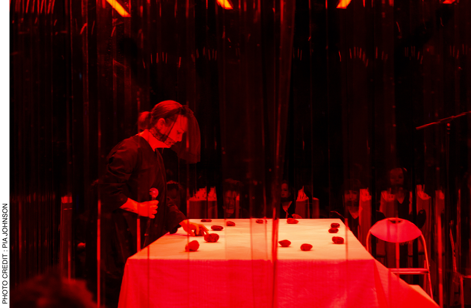 <p>Act 3, voice artist Jenny Barnes, who gives voice to the final possession, is surrounded by the seated choir as she touches stones placed on the platform/grave. Photo Credit: Pia&nbsp;Johnson.</p>