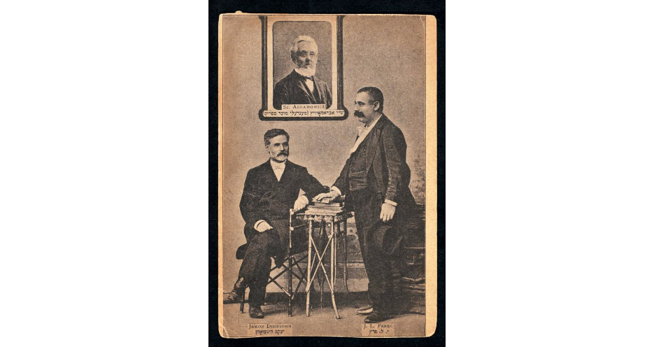 "<p>Jacob Dineson (seated), with <span class=""caps"">I. L.</span> Peretz and a framed portrait of Mendele Moykher-Sforim (Sholem Yankev Abramovitsh), ca. 1890s. Published in the Russian Empire, n.d. (<span class=""caps"">YIVO</span>)</p>"
