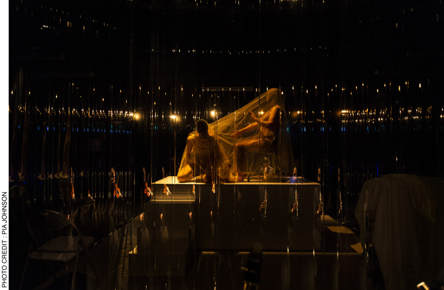<p>Performers Lauren Langlois and Yoni Prior in the opening Act of <i>Dybbuks </i>are shrouded atop the central raised platform of the stage, moving slowly around each other&#8217;s bodies. The musicians&#8217; reflections can be seen against the perspex curtain. Photo Credit: Pia&nbsp;Johnson.</p>