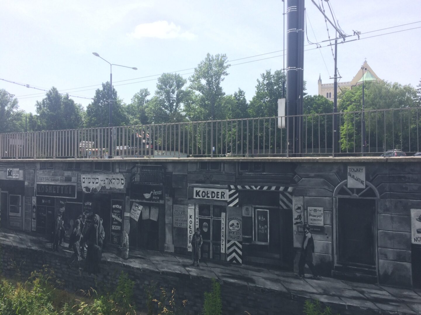 "<p>Mur­al along the Czechówka riv­er in Lublin, in the for­mer­ly Jew­ish neigh­bor­hood of Podzam­cze. For more infor­ma­tion, see <a href=""https://teatrnn.pl/pamiec/en/the-mural-alongside-the-czechowka-river/"">the The­ater <span class=""caps"">NN</span>'s web­site</a>. Pho­to by the&nbsp;author.</p>"