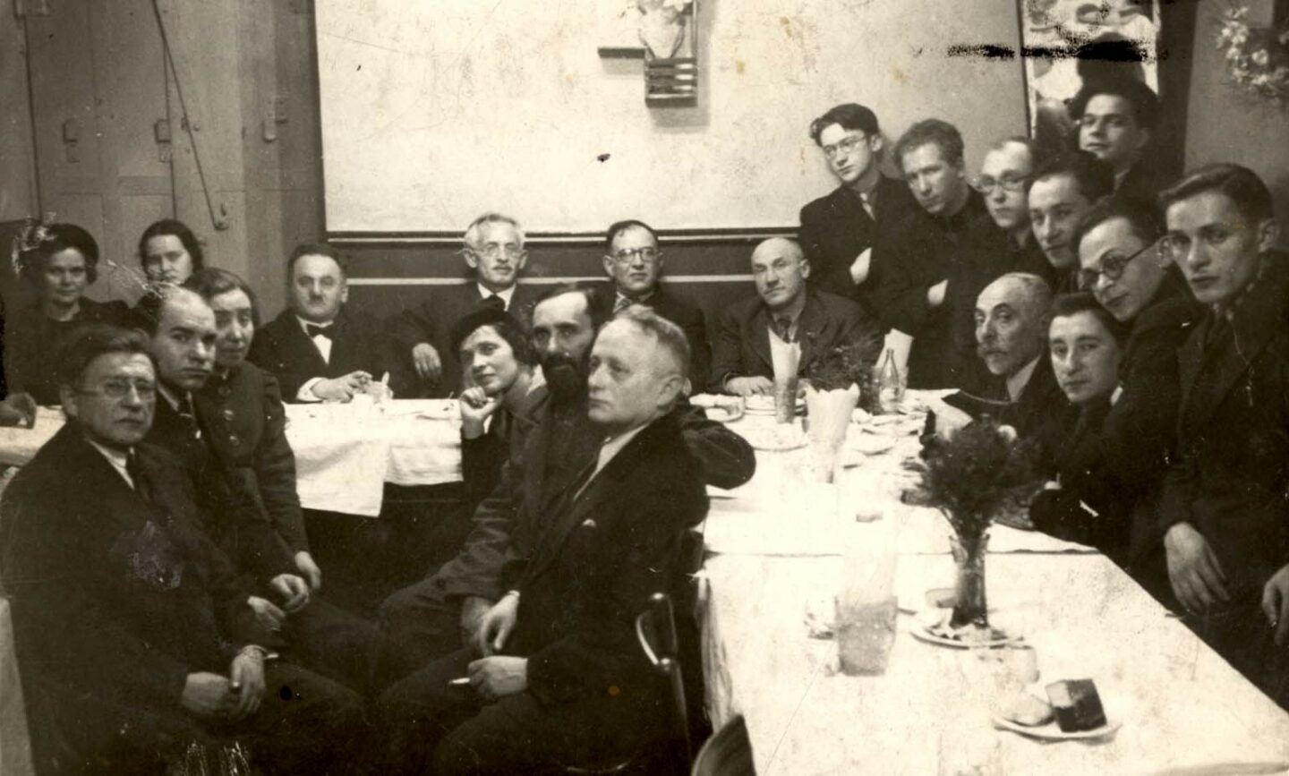 """<p>A farewell party for Falk Halperin at Velfke's restaurant in <span class=""""numbers"""">1938</span>, featuring a&nbsp;who's who of Vilne's Yiddishist cultural milieu. See below for a&nbsp;numbered identification of people in the photograph. Source: Yad Vashem, Photo Archive, Jerusalem, Archival Signature <sup class=""""numerator""""><span class=""""numbers"""">3380</span></sup>⁄<sub class=""""denominator""""><span class=""""numbers"""">296</span></sub>.</p>"""