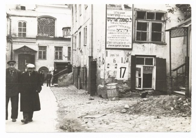 """<p>The <em>shulhoyf, </em>synagogue courtyard, Vilna, 1930s, showing a Yiddish advertisement for shipping agent L. Kopelovitsh. Source: <span class=""""caps"""">YIVO</span>Archives.</p>"""