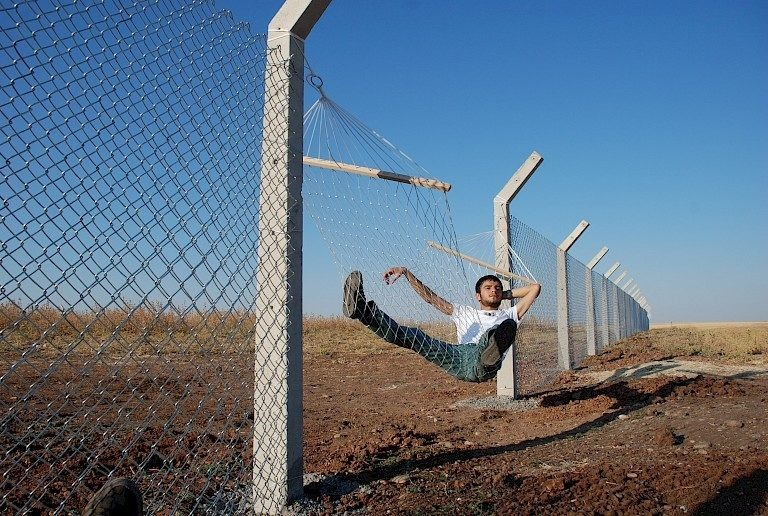 "<p>Image: Documentation of a performance by Murat Gök titled ""Border (Hammock),"" 2010. The artist installed a hammock on the border fence separating Turkey, Syria, and the Kurdish territories, playfully satirizing the absolutism of borders. <a href=""https://www.instituteforpublicart.org/case-studies/border/"">https://www.instituteforpublicart.org/case-studies/border/</a></p>"