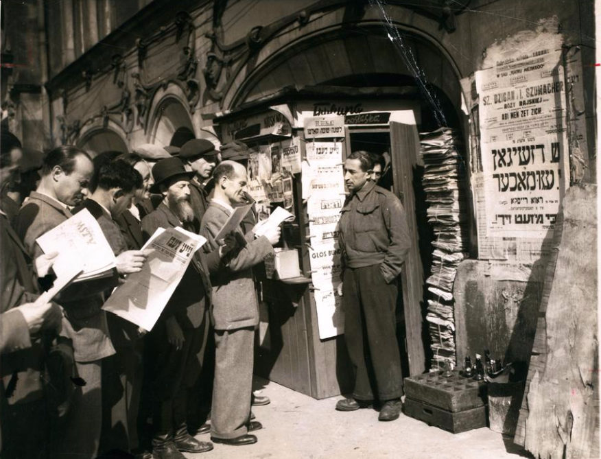 "<p>People at a newsstand reading Jewish newspapers, Wrocław, 1947. (Associated Press; print courtesy <span class=""caps"">YIVO</span>)</p>"