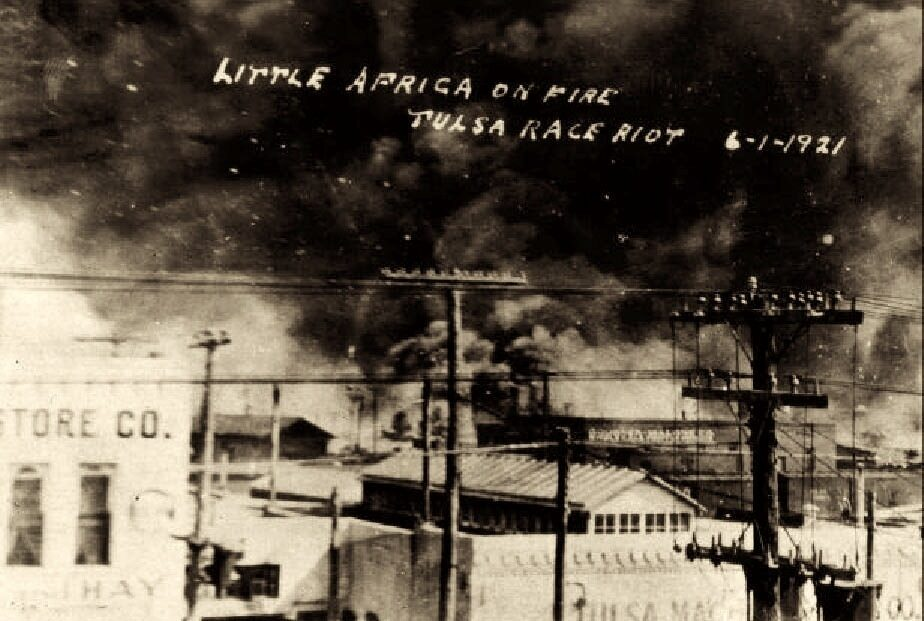 """<p>Postcard in the collection of McFarlin Library, University of Tulsa, via Wikimedia&nbsp;Commons.</p> <p><em>Little Africa on fire. Tulsa Race Riot, June <span class=""""numbers"""">1</span><sup class=""""ordinal"""">st</sup>, <span class=""""numbers"""">1921</span></em> This photo was taken from on top of the Santa Fe Freight office at <span class=""""numbers"""">1</span><sup class=""""ordinal"""">st</sup> St. and Elgin Ave., showing the fires on Archer towards Greenwood. The Goodner-Malone company (<span class=""""numbers"""">1</span>&nbsp;N. Frankfurt) building is in the center of the&nbsp;photo.</p>"""