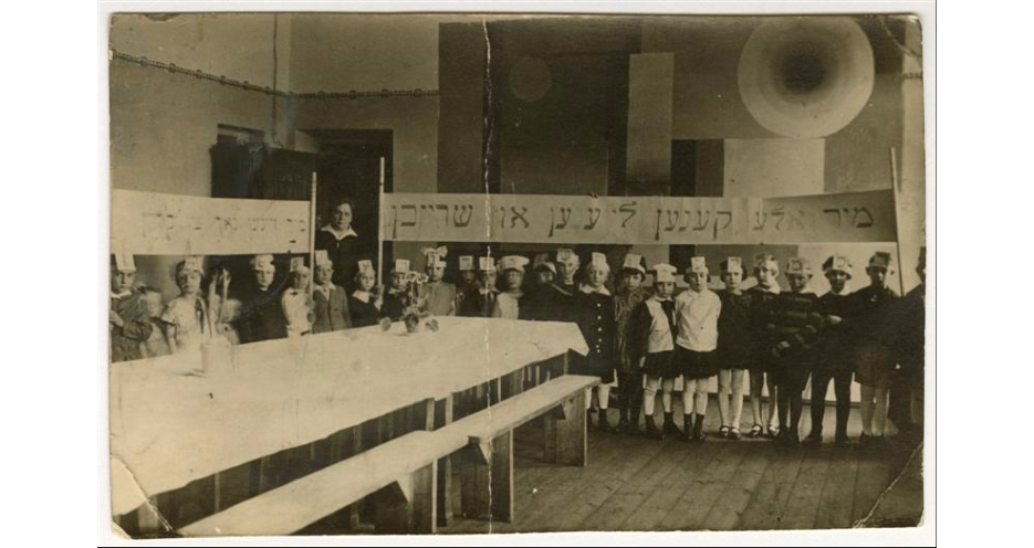 "<p>Stefania Shifra Szabad, wife of Jewish communal leader Tsemaḥ Szabad, with a class in a Yiddish school, Vilna, 1929. Children, wearing hats representing letters of the alefbeys (alphabet), hold a banner (right) that reads in Yiddish: ""We can all read and write.""&nbsp;(<span class=""caps"">YIVO</span>)</p>"