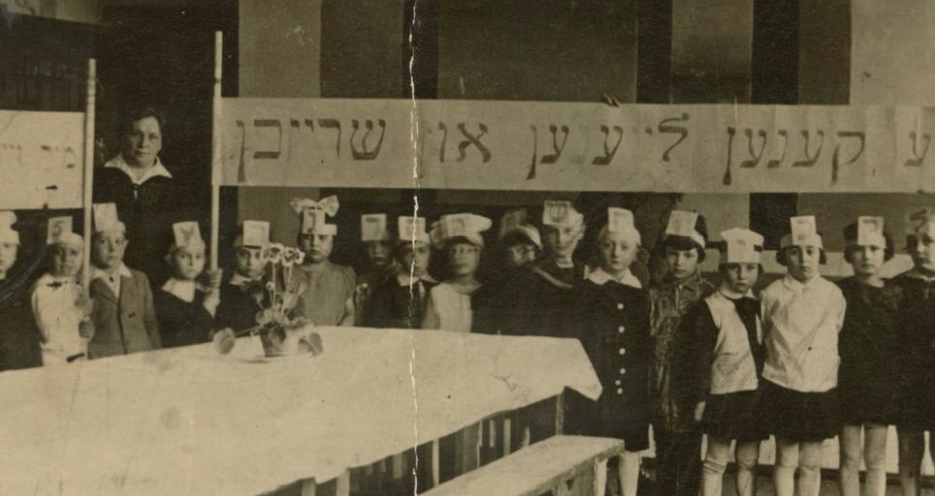 "<p>Stefania Shifra Szabad with a class in a Yiddish school, Wilno, 1929. Children hold a banner that reads: ""We can all read and write."" (Courtesy of&nbsp;<span class=""caps"">YIVO</span>)</p>"