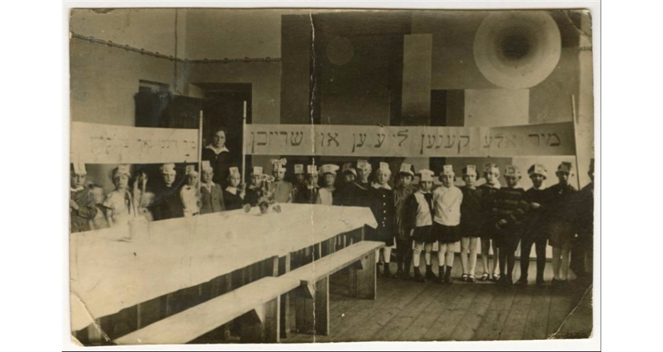 """<p>Stefania Shifra Szabad, wife of Jewish communal leader Tsemaḥ Szabad, with a&nbsp;class in a&nbsp;Yiddish school, Vilna, <span class=""""numbers"""">1929</span>. Children, wearing hats representing letters of the alefbeys (alphabet), hold a&nbsp;banner (right) that reads in Yiddish: <span class=""""push-double""""></span><span class=""""pull-double"""">""""</span>We can all read and write."""" (<span class=""""caps"""">YIVO</span>)</p>"""