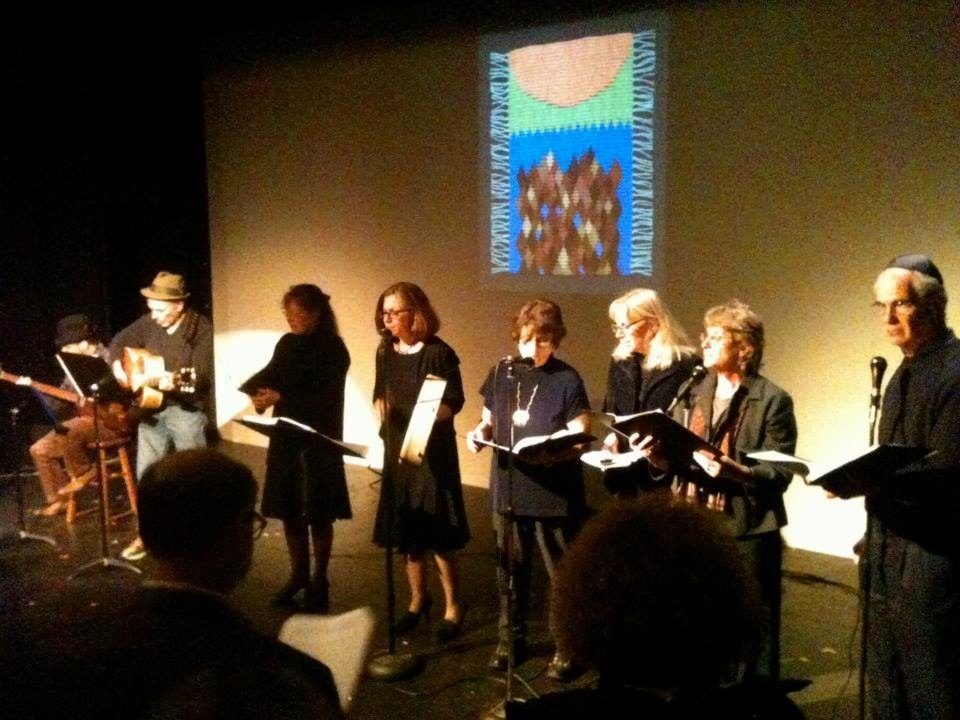 "<p><em>MameLoshn</em>, Oak Park's Yiddish singing group, commemorates Yom HaShoah. Projected behind them is an image of Berit Engen's tapestry, <i>""Mir zainen do!"" </i></p>"