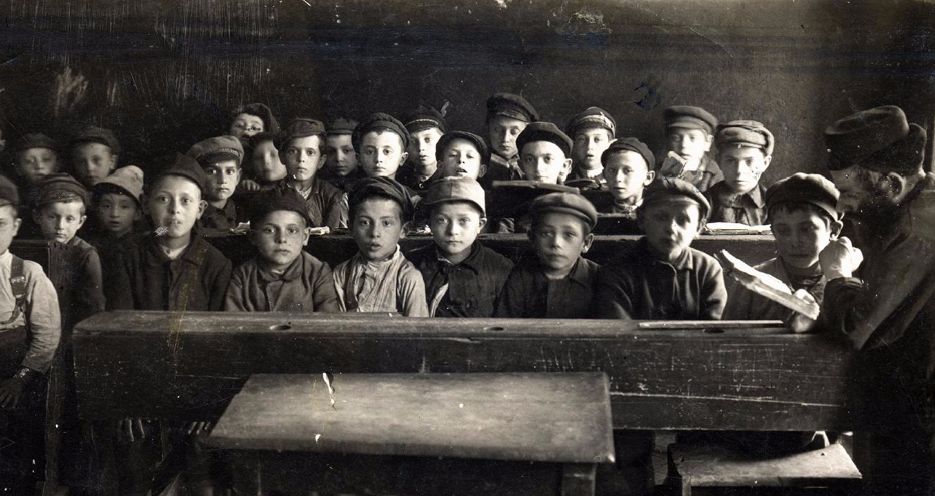 "<p>Children and teacher in a cheder, Warsaw, ca. 1917.&nbsp;(<span class=""caps"">YIVO</span>)</p>"