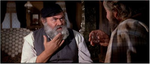 <p>Tevye is sitting with Leizer-Wolf, negotiating the latter's proposal of marriage to Tevye's daughter, Tzeitl. Still from <em>Fiddler on the Roof</em>&nbsp;(1971).</p>