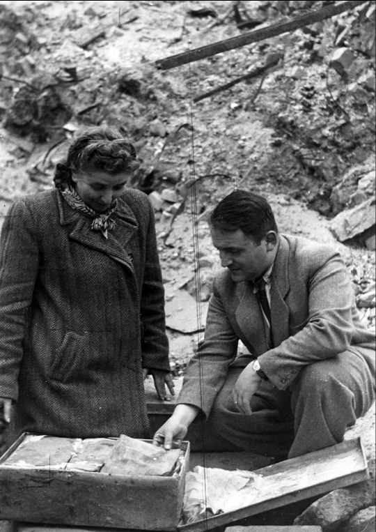 <p>Hersh and Bluma Wasser, surviving members of Oyneg Shabes, with a portion of the secret archive buried in tin containers for safekeeping and recovered soon after the war in the ruins of the Warsaw ghetto. (The Ghetto Fighters' Museum/Israel)</p>