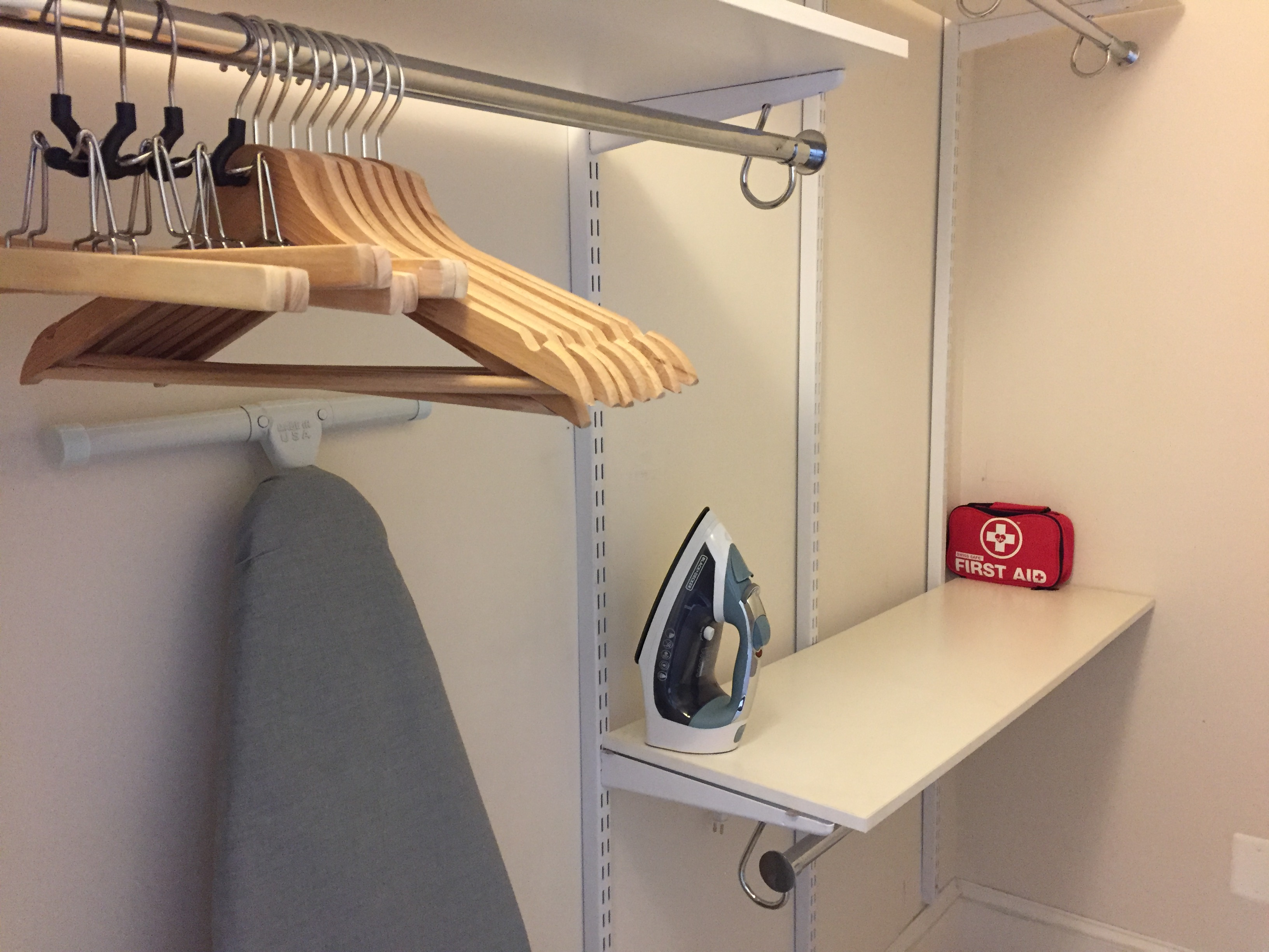 Walk-in closet in Master bedroom with hangers, iron, ironing board and first-aid kit.