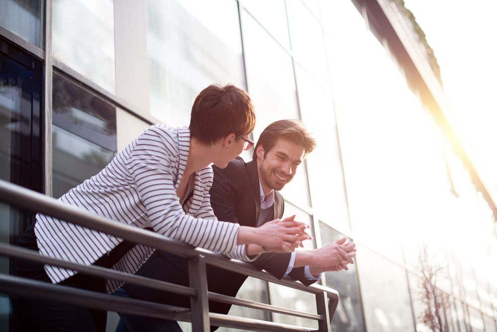 Business people talk on a balcony