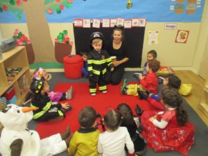 Children in the Red Room (2s) at our 86th Street location participate in a Halloween costume show and share.