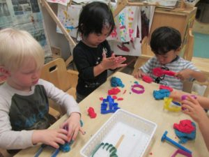 Our youngest students hard at work! The children here are bolstering a variety of skills while at the play dough table: strengthening their hands for future writing activities; learning to share tools; engaging in both parallel and cooperative play; and working on expressive and receptive language skills...just to name a few!