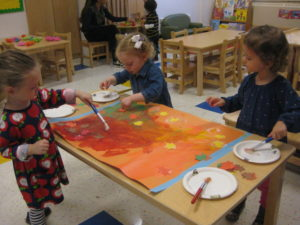 A 2s class at 76th Street worked collaboratively to create a fall mural using fall-themed colors: red, orange, and yellow.