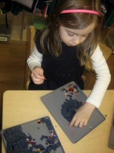 "A child played with ""night sky"" play dough. The play dough provided a great tactile experience; the dark background allowed the small jewels to stand out, much like stars do in the night sky."