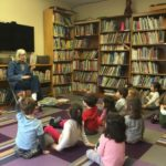 Children build up their attention spans by listening to stories read aloud in a whole group during Library class.