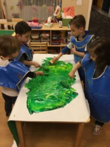 A whole group Earth project, using green paint to represent land.