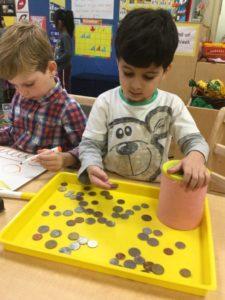 Exploring with coins in an IPS Junior Kindergarten classroom.