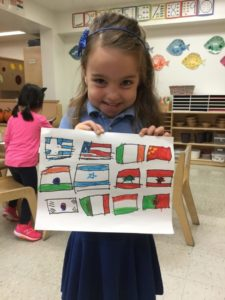 A pre-K student with her work in preparation for our United Nations Day celebration.