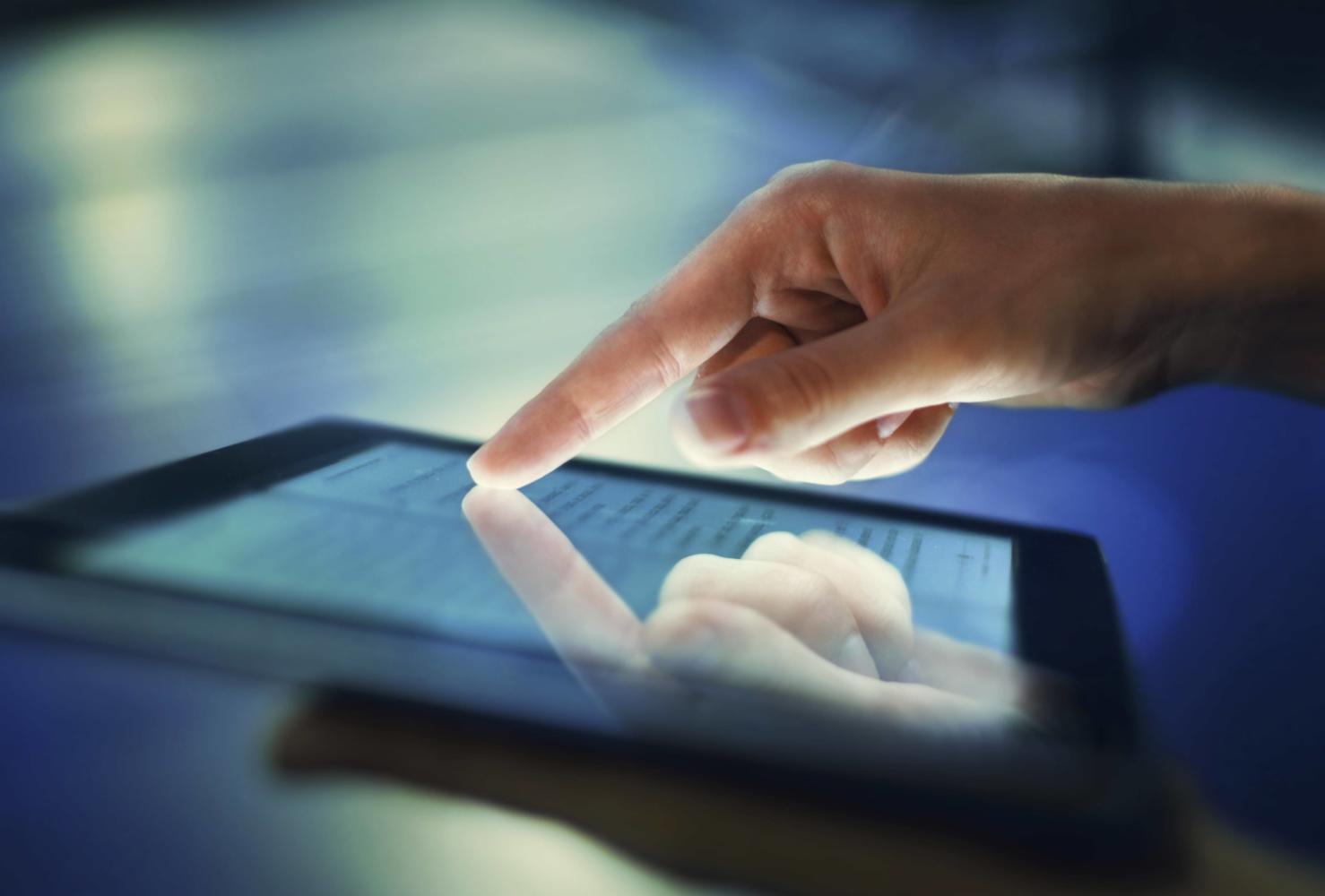 Finger touching tablet screen