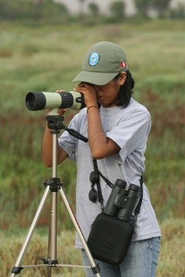 Woman looking through a spotting scope