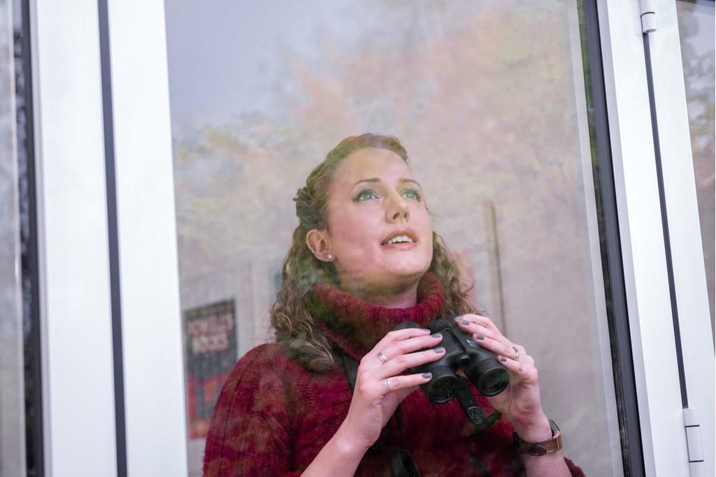 mulher a observar aves à janela