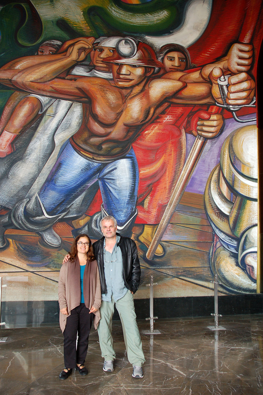 Director Lorena Manriquez with co-director Miguel Picker under a Siqueiros painting.