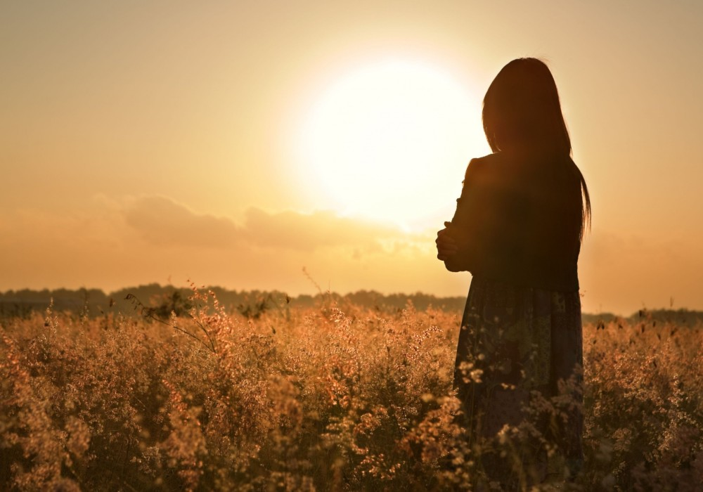 Silhouette-of-a-woman-standing-in-flower-meadow-watching-beautiful-sunset
