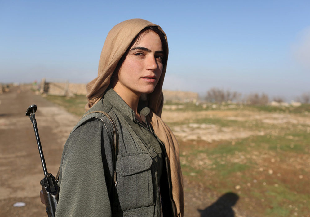 A Kurdish woman stands in resistance to ISIL. Photo Credit: Times UK