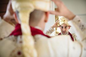 Indian man putting on wedding turban