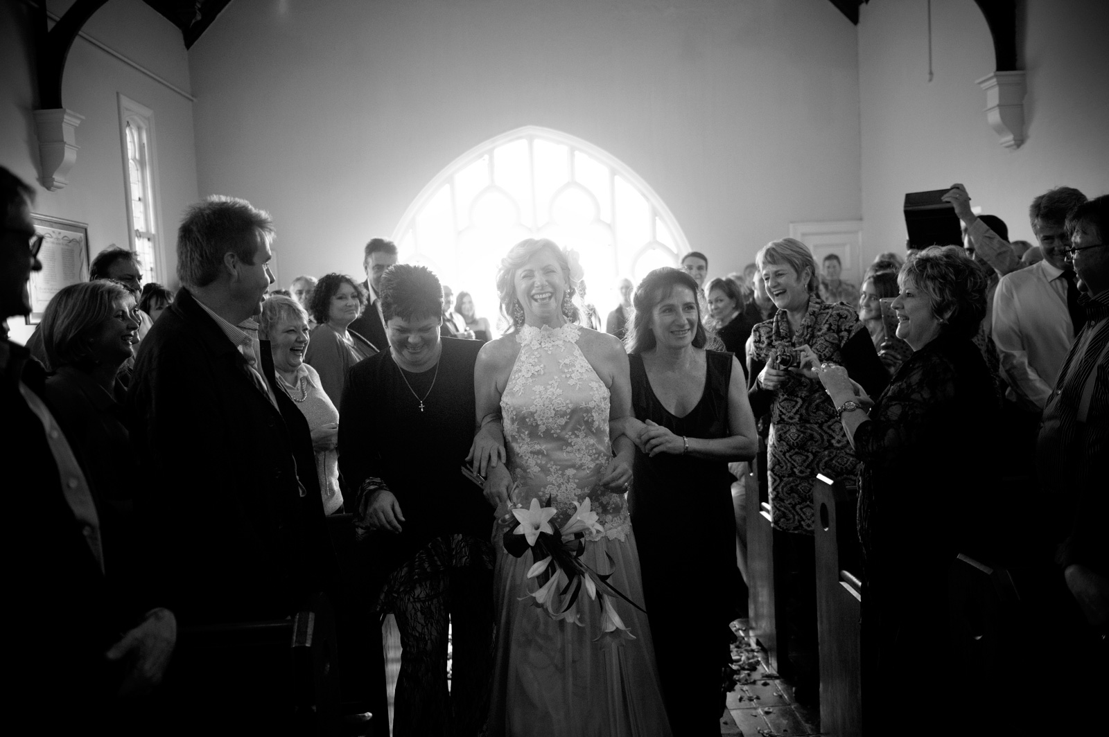 women walk bride down the aisle