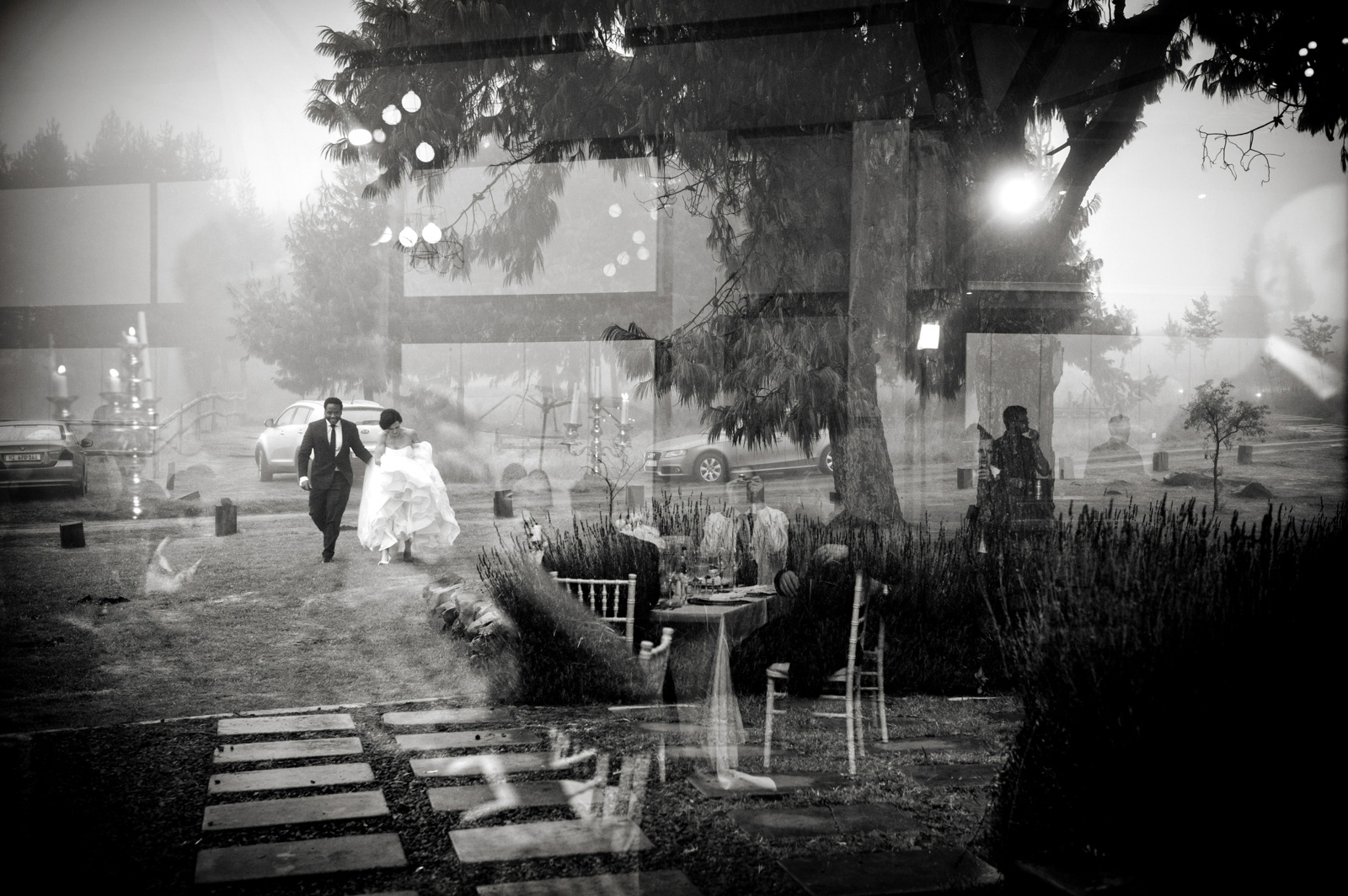 bride and groom running in the rain