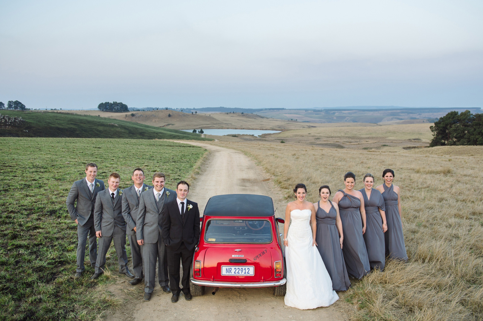 bridal party on a road with a car