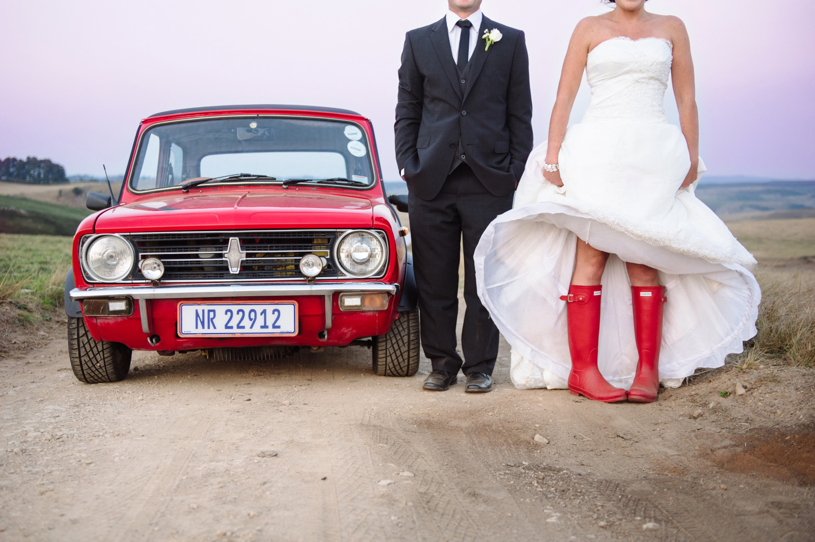bride in boot with groom by car