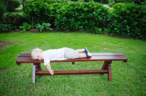 child sleeping on bench