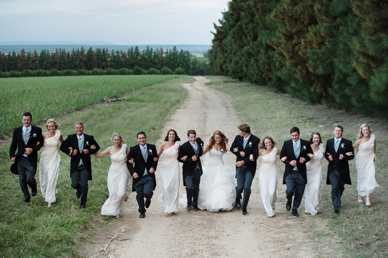 Bridal party running in field
