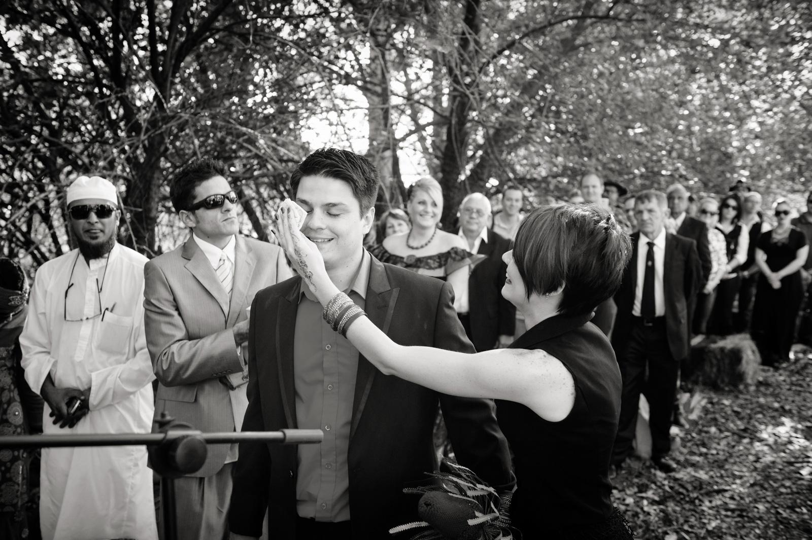 bride in black dress wiping grooms tears