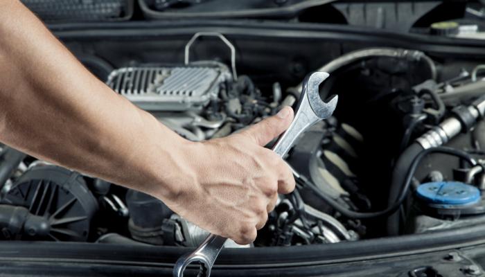 Auto Technician Working Under The Hood