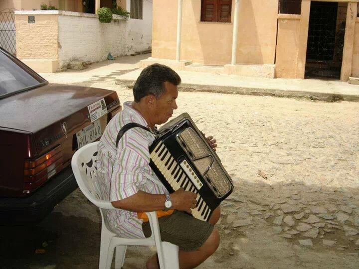 Comerciante Domingos Saturnino (im), tocando o acordeon na calçada de casa na Rua Robert Braquehais, em Maranguape. Foto Dadynha Saturnino