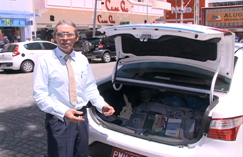 Taxista carrega livros no porta-malas do carro (FOTO: Reprodução TV Jangadeiro)